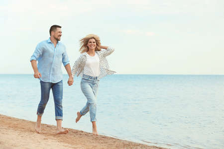 Happy romantic couple running together on beach, space for text