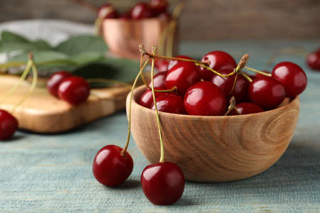 Wooden bowl of delicious cherries on blue table, closeup view. Space for text