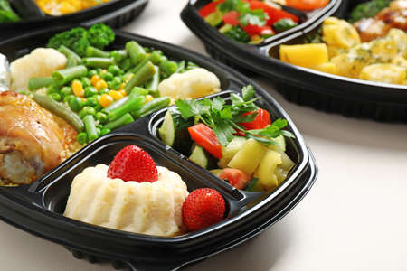 Lunchboxes with different meals on white table, closeup. Healthy food delivery Banco de Imagens
