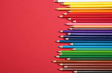 Colorful pencils on red background, flat lay. Space for text Banco de Imagens