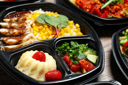 Lunchboxes with different meals on table, closeup. Healthy food delivery