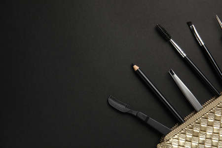 Set of professional eyebrow tools on black background, flat lay. Space for text