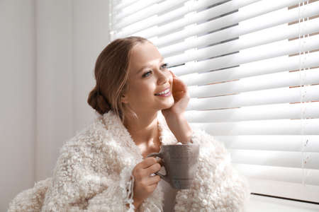 Beautiful young woman with cup of hot drink near window at home. Winter atmosphere