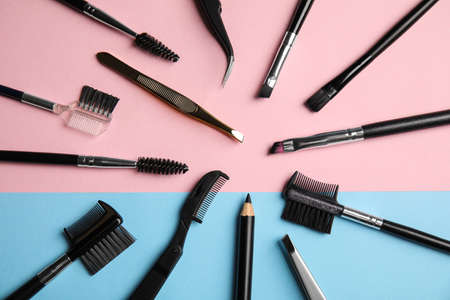 Set of professional eyebrow tools on color background, flat lay Фото со стока