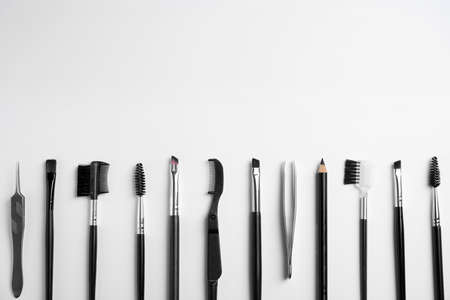 Set of professional eyebrow tools on white background, flat lay. Space for text Фото со стока