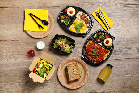 Lunchboxes with different meals on wooden table, flat lay. Healthy food delivery