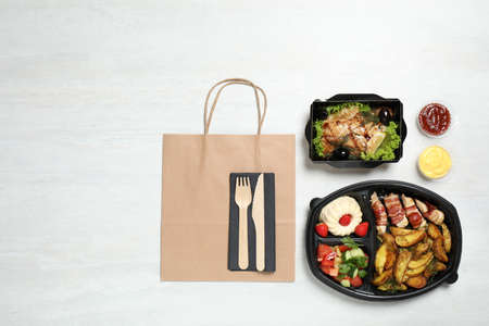 Flat lay composition with lunchboxes on white table. Healthy food delivery
