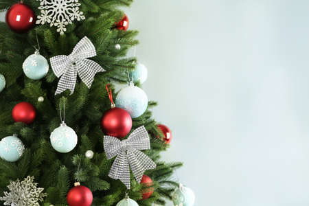 Beautiful Christmas tree with decor against light grey background. Space for text
