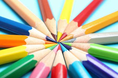 Composition avec des crayons colorés sur fond bleu clair, gros plan