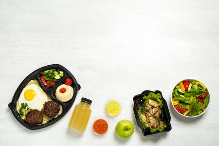 Flat lay composition with lunchboxes on white table, space for text. Healthy food delivery Banco de Imagens