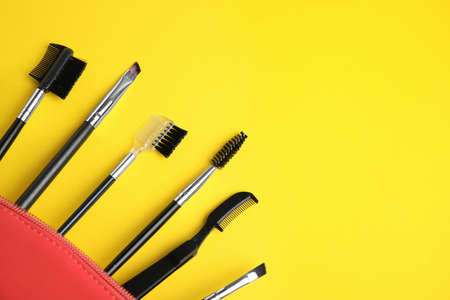 Set of professional eyebrow tools on yellow background. Space for text Фото со стока