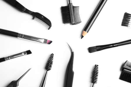Set of professional eyebrow tools on white background, top view Фото со стока