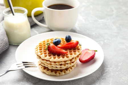 Tasty breakfast with wafers served on light grey marble table