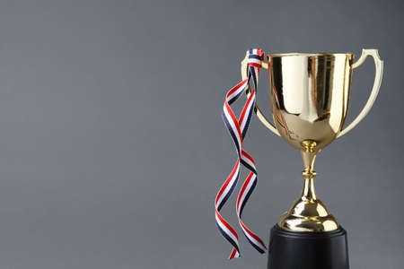 Golden trophy cup with ribbon on grey background. Space for text