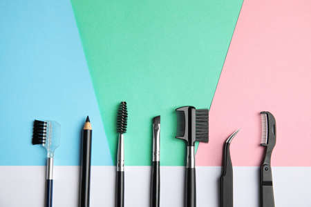 Set of professional eyebrow tools on color background, flat lay. Space for text Фото со стока