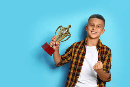 Happy boy with golden winning cup on blue background