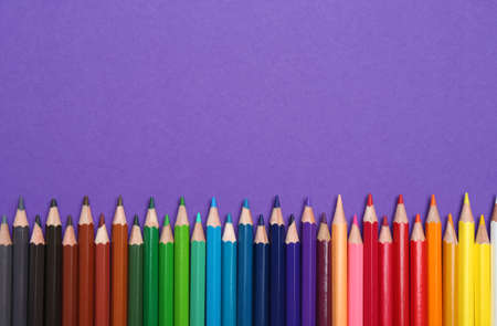 Colorful pencils on purple background, flat lay. Space for text