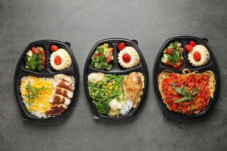 Lunchboxes with different meals on grey table, flat lay. Healthy food delivery