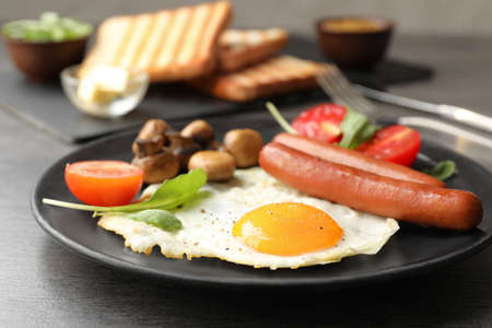 Tasty breakfast with fried egg on table, closeup