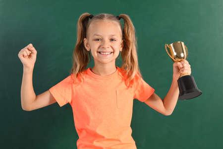 Happy girl with golden winning cup near chalkboard
