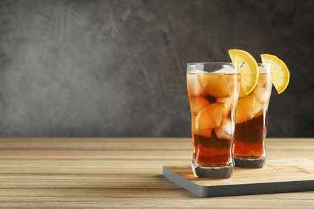 Glasses of tasty ice tea with lemon on wooden table against grey background, space for text