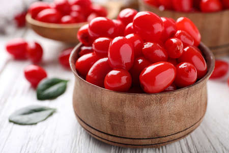 Fresh ripe goji berries in bowl on white wooden table
