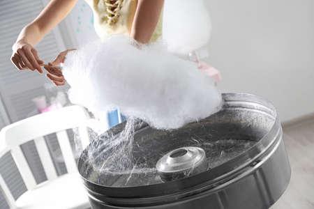Woman making cotton candy using modern machine indoors, closeup Reklamní fotografie