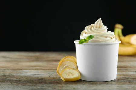 Cup with tasty frozen yogurt and banana on wooden table. Space for text