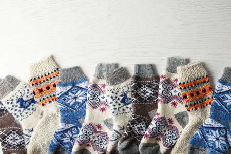 Soft knitted socks on white wooden background, flat lay with space for text. Winter clothes