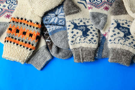 Soft knitted socks on blue background, flat lay. Winter clothes Фото со стока