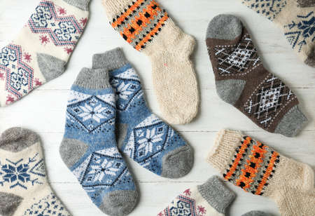 Different knitted socks on white wooden background, flat lay