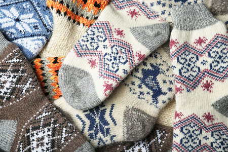Different knitted woolen socks as background, closeup Фото со стока