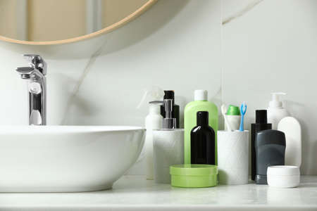 Stick deodorant and different toiletry on countertop in bathroom