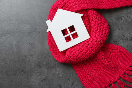 Wooden house model and red scarf on grey stone background, top view. Heating efficiency