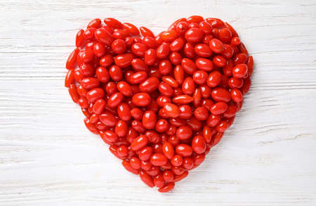 Heart shaped pile of fresh ripe goji berries on white wooden table, top view Stok Fotoğraf