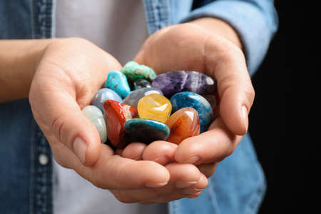 Young woman holding many beautiful gemstones, closeup