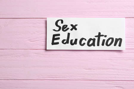 Piece of paper with phrase SEX EDUCATION on pink wooden background, top view