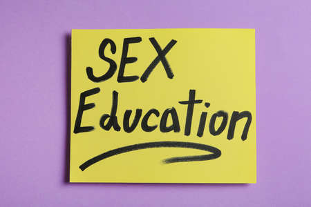 Note with phrase SEX EDUCATION on violet background, top view