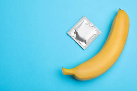Condom with banana and space for text on light blue background, flat lay. Safe
