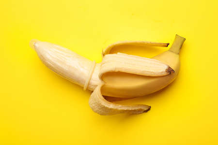 Banana with condom on yellow background, top view. Safe sex Stock Photo
