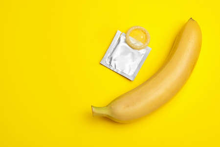 Condom with banana and space for text on yellow background, flat lay. Safe sex
