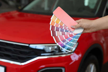 Young woman holding palette with color samples near red car, closeup. Space for text Banco de Imagens