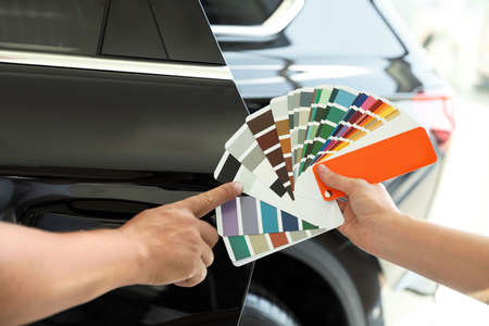 Man choosing color for car painting on palette at service station, closeup Banco de Imagens