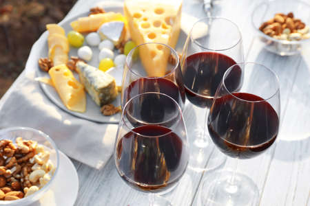Red wine and snacks served for picnic on white wooden table outdoors Stock Photo