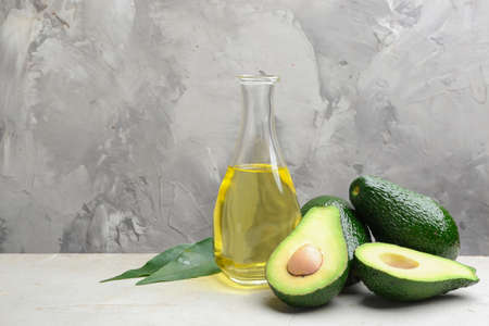 Bottle of natural oil and avocados on table against grey stone background. Space for text