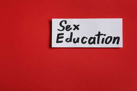 Piece of paper with phrase SEX EDUCATION on red background, top view, Space for text Stock Photo