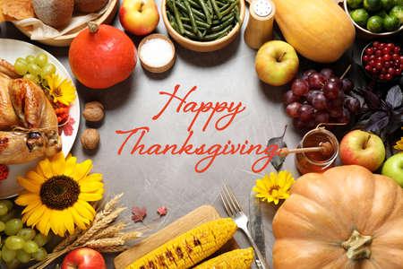 グレーのテーブルにおいしいロースト七面鳥、秋野菜や果物とフラットレイ構成。ハッピー感謝の日 写真素材