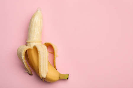 Banana with condom and space for text on pink background, top view. Safe sex