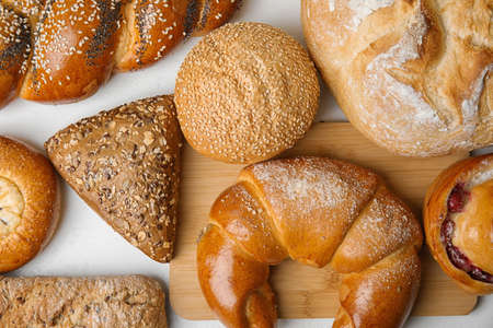 Fresh breads and pastries on white table, flat lay