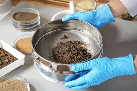 Científico pulverizando y tamizando muestras de suelo en la mesa, primer plano. Análisis de laboratorio